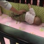 A doll shows how a real infant can suffocate on crib bumper pads